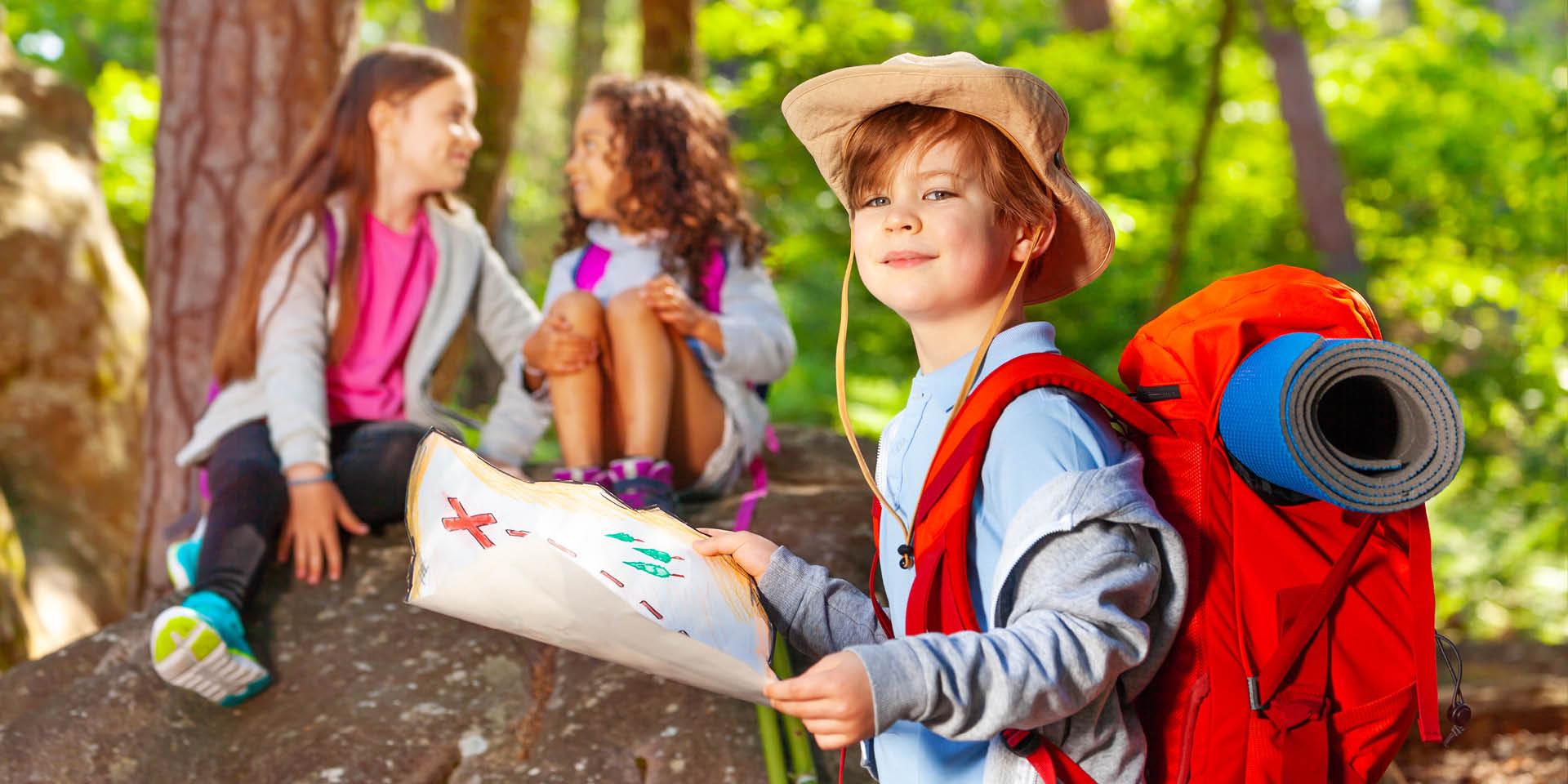 Ein Kind steht in Abenteurer-Ausrüstung und mit einer Schatzkarte im Wald. Hinter ihm sitzen zwei Mädchen auf einem Stein.