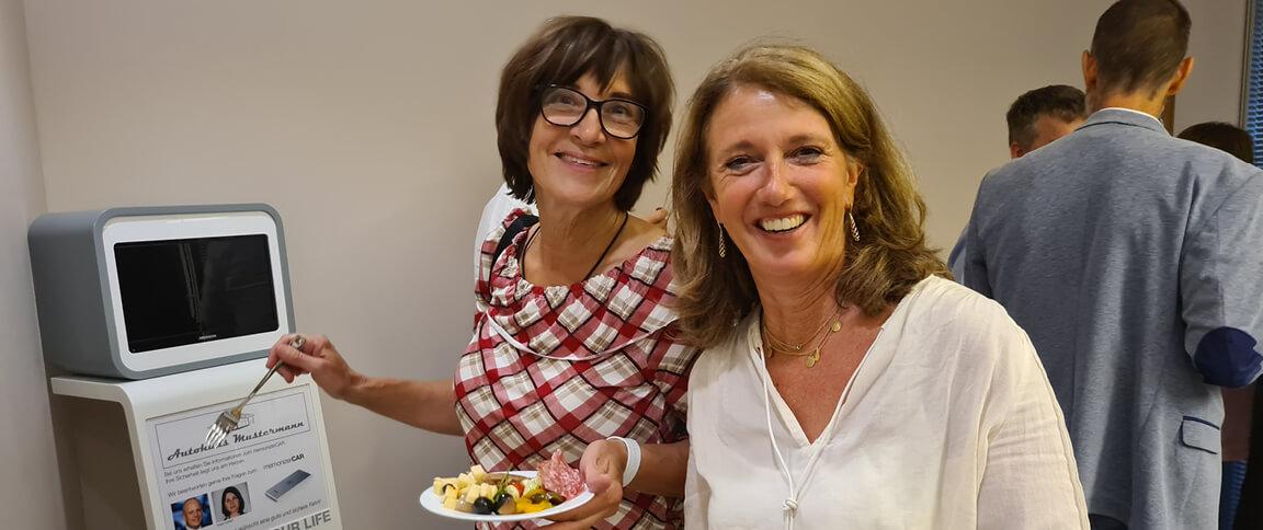 zwei lachende Frauen am Buffet mit Blick in die Kamera