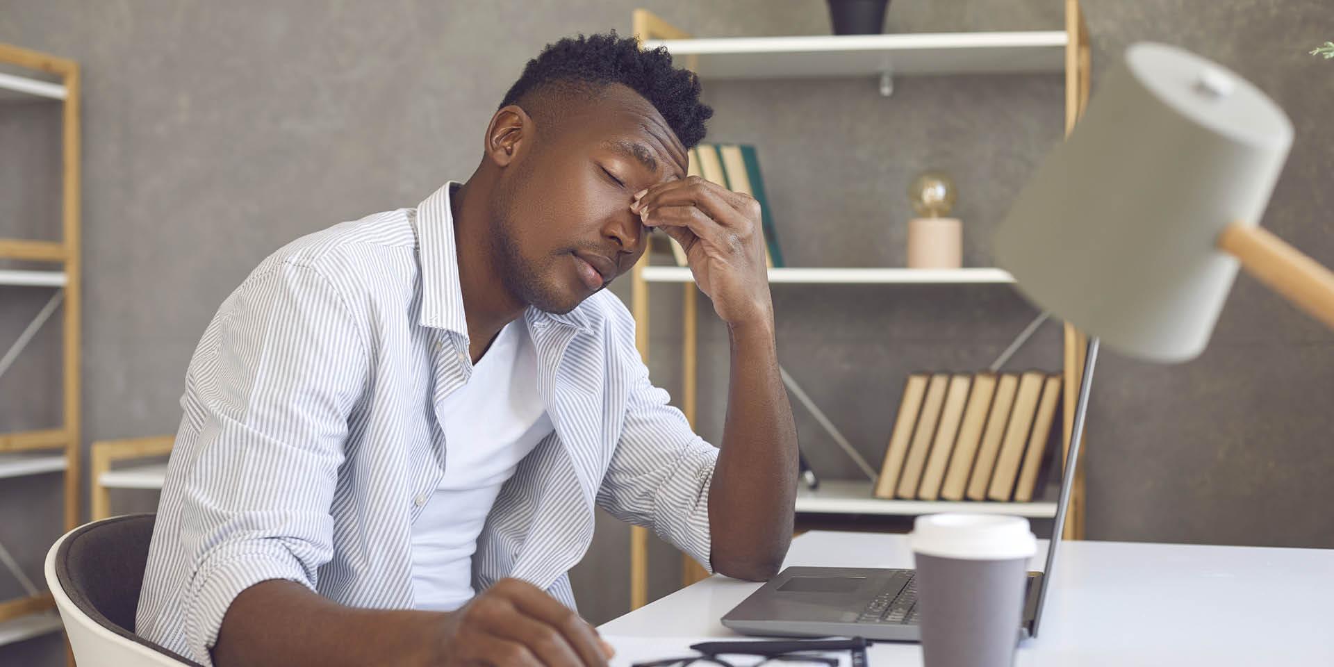 Ein Mann sitzt vor einem Laptop und macht einen müden Eindruck.