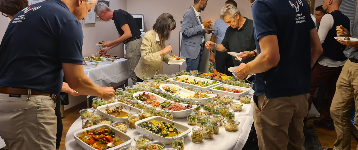 Seminarteilnehmer an einem Buffet am runden Tisch