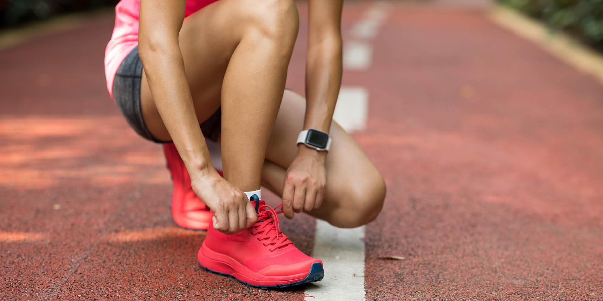 EIne Läuferin schnürt sich auf einer Tartanbahn pinke Laufschuhe zu und trägt dabei eine Smartwatch am Arm.