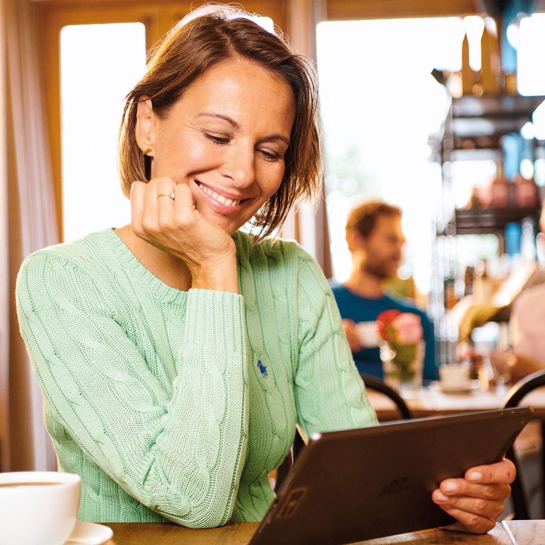 Eine Frau im Café sitzt an ihrem iPad