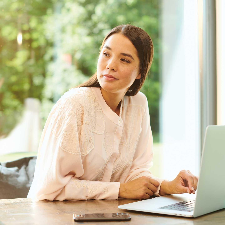 Frau mit skeptischem Blick und Smartphone und Tablet am Tisch