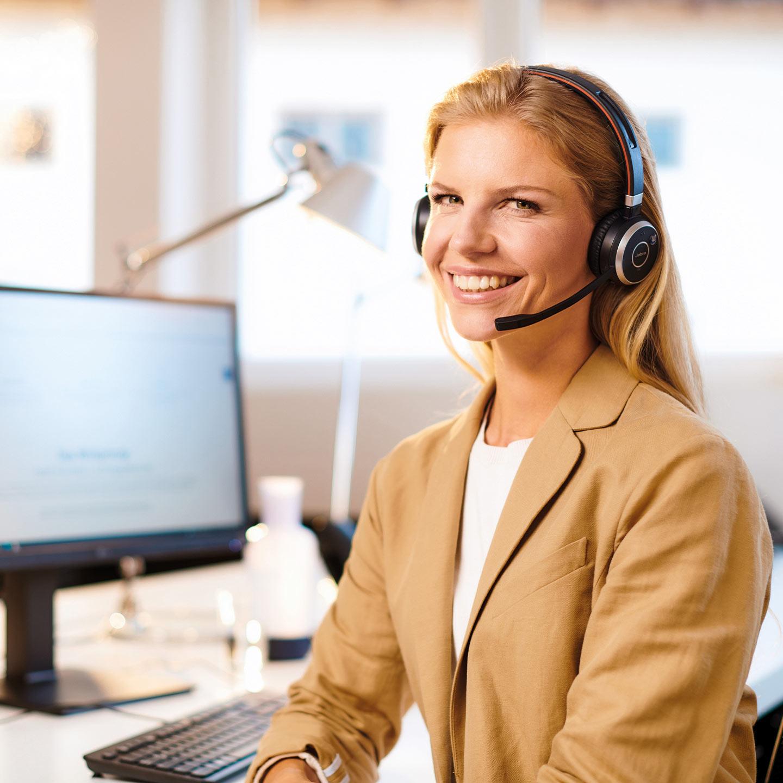Frau am Schreibtisch mit Headset telefonierend