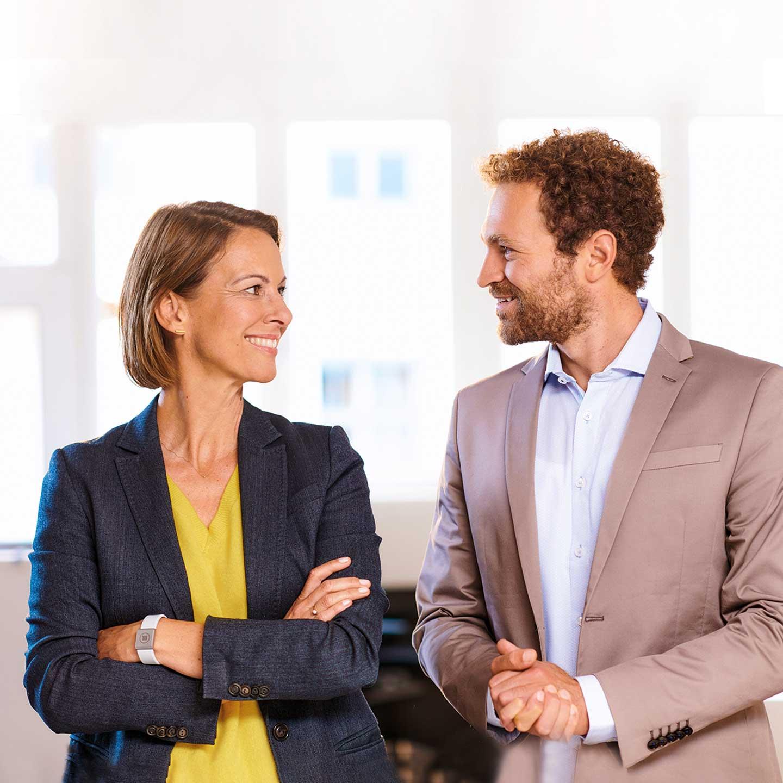 Eine Frau und ein Mann stehend sich gegenüber und lächeln sich an