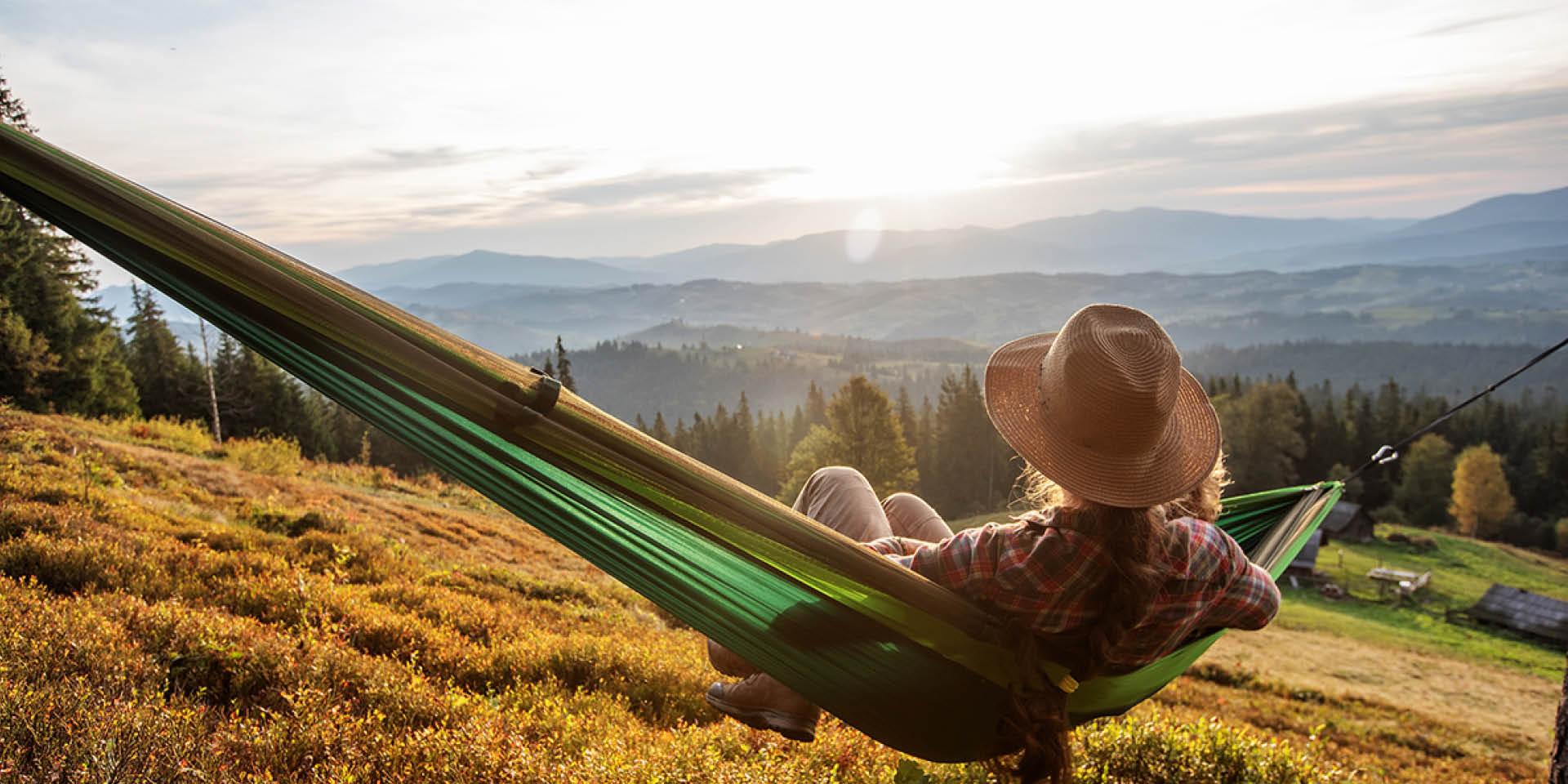 Frau mit Hit sitzt in einer Hängematte und blickt auf ein Berg-Panorama in der Abendsonne