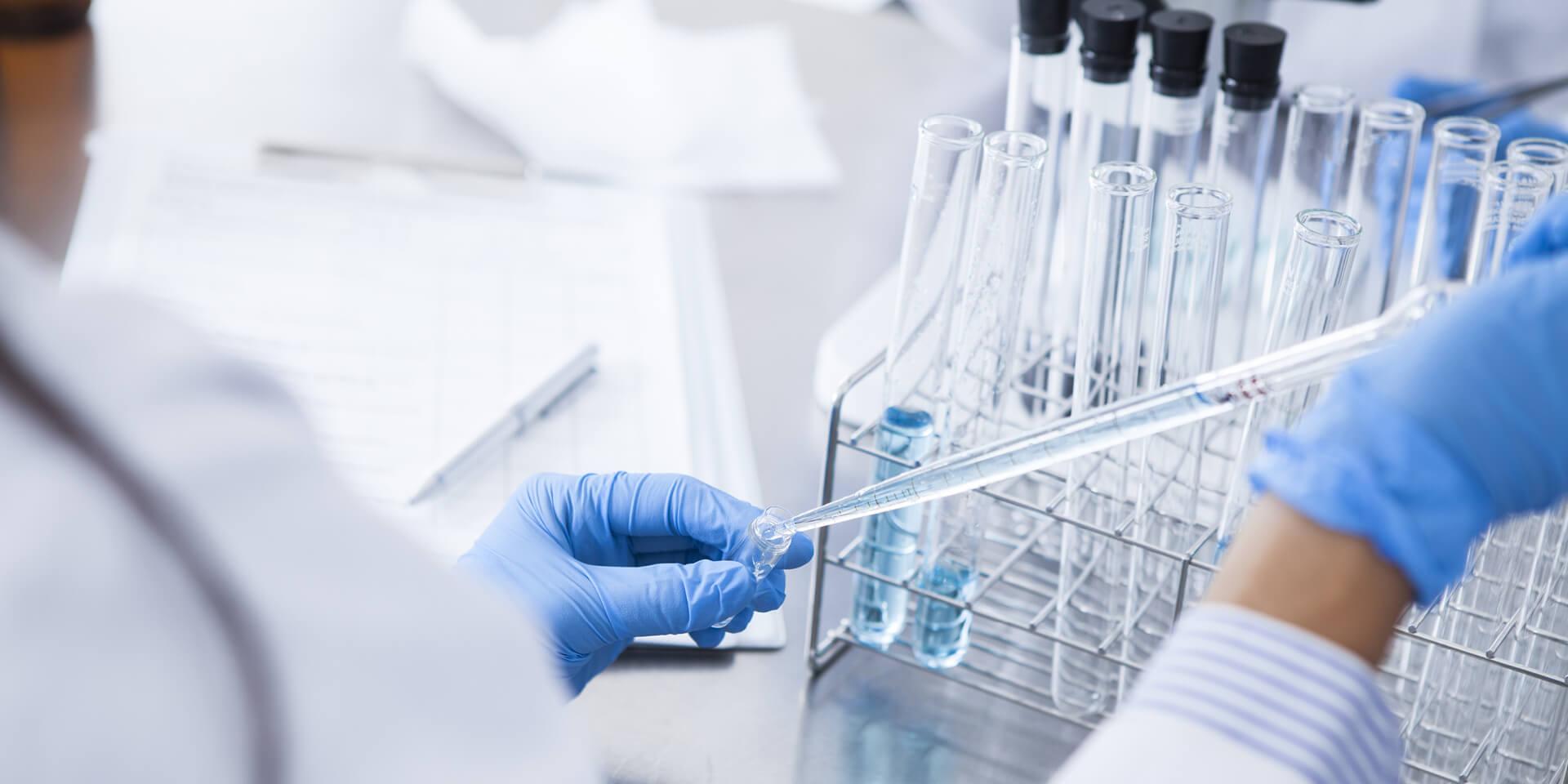 Wissenschaftler:in beim entnehmen einer Probe mit einer Pipette