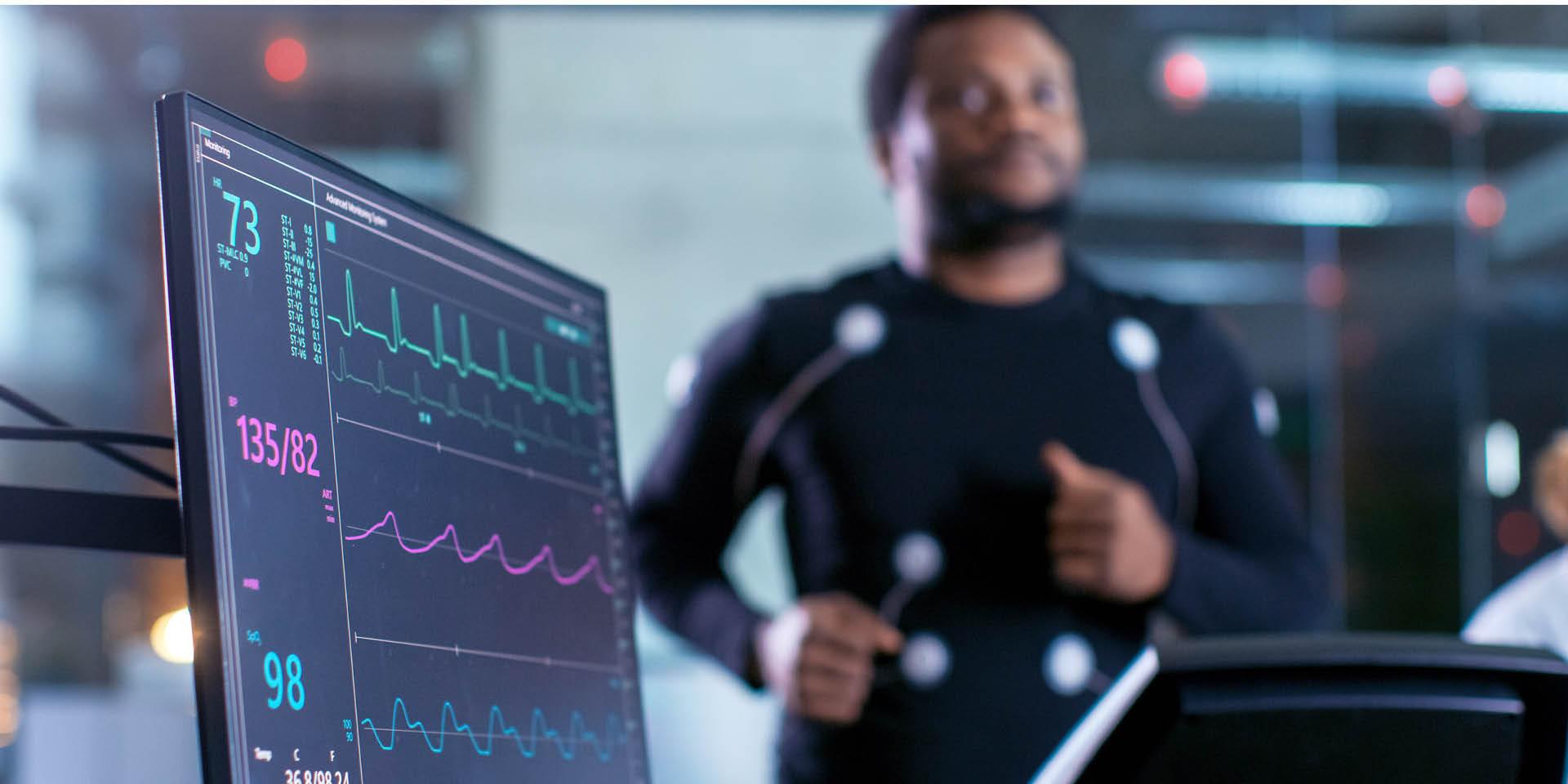 Ein Mann läuft auf einem Laufband und ist an ein EKG angeschlossen