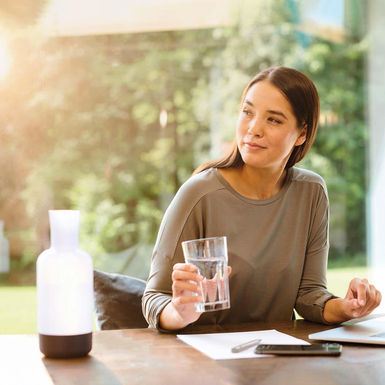Eine Frau im Homeoffice vor ihrem Laptop mit einem Glas Wasser in der Hand